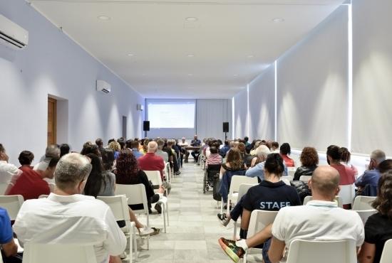La sala congressi con luci soffuse e videoproiezione